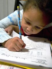 "Aisha Jones, 6, concentrates on her reading homework at her home in Bolingbrook, Ill., Feb. 15, 2006. Though Aisha scored well on her annual tests, her mother, Toia Jones, a school teacher of 12 years, says she is concerned that a loophole in the No Child Left Behind Act is enabling states and schools to avoid taking concrete measures to eliminate an ""achievement gap"" between white and minority students."