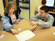 "Cessna Elementary School Principal Chris Wendt listens as student Jocelyn Sanbrano talks about fractions at the school in Wichita, Kan., Thursday, Feb. 16, 2006. Sanbrano says she likes taking her tests on the computer: ""Your hands don&squot;t cramp up,"" she said."