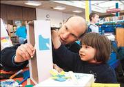 Lawrence resident Dietrich Earnhart puts on a puppet show with stick figures and a shoe box that he and his daughter, Amanda, 3, created in March at the Lawrence Public Library, 707 Vt. Lawrence officials would like to either expand or enhance the existing site, or build a new library downtown.