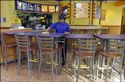 Dipika Patel, of Lawrence, works at the renovated Taco Bell restaurant at Sixth and Michigan streets. The new interior of the store is brighter and has more modern-looking furniture.