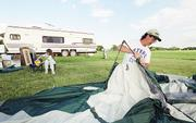 Terry Pickens wrestles with his tent as Darci Rodecap, 9, takes a seat. Pickens was setting up his camp for Memorial Day last year at Clinton Lake State Park. He and other Kansans would be able to use state parks for free under a plan endorsed by Gov. Kathleen Sebelius.