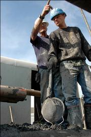 Mike Glaze, owner of Glaze Drilling of Spring Hill, tells crew member Jim Curry what he's looking for as he drills a new well west of Gardner in November 2005. The area near Wellsville has reaped profits for oil prospectors.