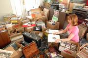 Peggy Sampson, assistant development director for the Kansas Audio-Reader Network, browses through donated records that will be sold at the studio's annual fundraiser. Because Audio-Reader lost the space used to store the donated items for the sale, the Lawrence-based radio reading service is no longer able to receive new donations.