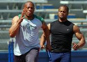 Maurice Greene, left, takes the baton from teammate Kaaron Conwright during a practice session Thursday.