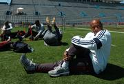 Former Olympic gold medalist Maurice Greene stretches prior to his workout at Memorial Stadium. Greene - and most of the other ballyhooed athletes who will compete in the GOLDZONE II portion of the Kansas Relays on Saturday - worked out Thursday.