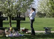 Aimee Eubanks holds her 7-month-old son, Caden, Thursday as she visits the grave of Corey DePooter, in Littleton, Colo. DePooter was among the 12 students and one teacher killed April 20, 1999, in the Columbine High School shooting.  Aimee's husband, Stephen, was DePooter's best friend and was shot during the massacre at the school.