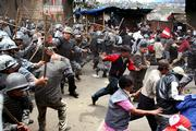 Police with batons chase protesters during a demonstration in Katmandu, Nepal. Nepalese police opened fire Thursday on thousands of pro-democracy protesters who defied a curfew to march toward the capital, killing at least three and wounding dozens more, witnesses and hospital officials said.