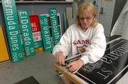 Debbie Rollins, a traffic control technician with the city's Public Works Division, finishes up a street sign earlier this week. Rollins creates many signs from start to finish for the city.