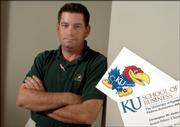Christopher Anderson, associate professor in the School of Business has a Jayhawk logo on the back of each of his business cards. This flies in the face of new KU standards that place the beloved Jayhawk only on the business cards and stationary of those in the athletic department and the alumni association.
