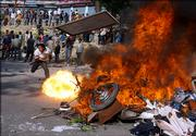 An opposition party supporter throws furniture taken from an apartment believed to be belonging to the police into a fire as a motorcycle tank catches fire at a demonstration in Kalanki, on the western edge of Katmandu, Nepal, Friday April 21, 2006, where four people were killed on Thursday. A massive crowd of protestors rallied on the outskirts of Katmandu Friday, defying a government-imposed curfew a day after security forces opened fire on demonstrators in a deadly display of force.