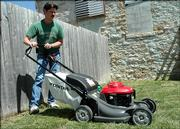"""Jim Kuester, sales manager at Fleetwood Mower and Rental demonstrates a new Honda HRX mower with """"Versamow"""". The mower has two blades for better mulching and a way to adjust how much you bag and how much you leave behind on your yard."""