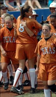 At center, Texas Longhorns pitcher Cat Osterman, #8, hugs Amber Hall after Hall's seventh-inning home run lifted Texas to a 1-0 win over Kansas Saturday in front of a record crowd at Arrocha Ballpark.