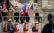 Members of the National Socialist Movement, protected by chain link fence and Michigan State troopers, rally at the state Capitol in Lansing, Mich., Saturday, April 22, 2006. The white supremacists said they were taking a stand against illegal immigration, but their appearance was met by boos from counterprotesters.