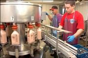 Tim Iwig and his nephew, Andrew Byler, 26, make up part of the chocolate milk-bottling assembly line.