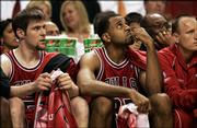 Chicago Bulls' Malik Allen, center, and Andres Nocioni of Argentina, left, sit on the bench as the Miami Heat pulls ahead during the third quarter of an NBA basketball first-round playoff game at the American Airlines Arena Monday April 24, 2006, in Miami. The Heat won 115-108.