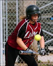 Lawrence High's Caitlin Bowlin lays down a bunt against Shawnee Mission West. The Lions split two games Monday at Holcom Sports Complex, beating Leavenworth, 8-3, but falling to Shawnee Mission West, 6-2.