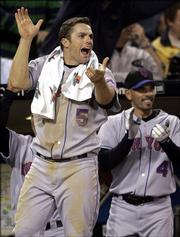 New York Mets' David Wright (5) and Chris Woodward lead the team out of the dugout in celebration as the Mets' Julio Franco's two-run home run gave the Mets a 3-2 lead in the eighth inning against the San Diego Padres, in this April 20, 2006 file photo  in San Diego. With uncommon poise, perspective and get-dirty enthusiasm, Wright is becoming one of baseball's toughest outs and a Big Apple icon all at once.