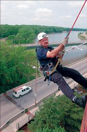 Byron Miller rappels down the west side of City Hall Monday afternoon. Miller was one of several members of Lawrence Douglas County Fire & Medical practicing their rappelling skills on different buildings to gain familiarity with the equipment.