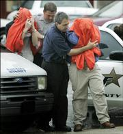 Two of five Riverton High School students are led to a hearing at the Cherokee County Courthouse in Columbus, Kan., Monday, April 24, 2006. They are suspects in a school shooting plot.