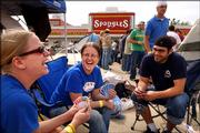 Kansas University students Ginny Heitschmidt, Hutchinson freshman, left, Haley O'Neal, Hutchinson freshman, and Travis Mize, Wichita junior share a laugh as they play a game of UNO while camping outside the new Spangles location at Kasold and Sixth streets. The group had been camping in the parking lot of the restaurant since 4:30 a.m. and plan to stay until 6:30 p.m. Tuesday when the store opens to be a few of the first 100 customers to the restaurant and by doing so will receive 52 vouchers for a free meal for the next year.