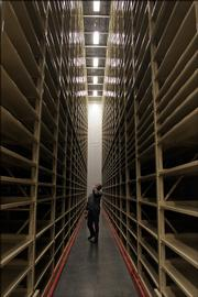 Gary Lawson, engineering project manager at Kansas University, glances up at the 38-foot tall shelves inside the new Library Annex on west campus.  Lawson was one of many on hand for Wednesday's ribbon-cutting ceremony for the new storage building.