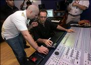 "Hip-hop star Pitbull, left, whose real name is Armando Perez, talks with producer Eduardo Reyes as he mixes a track while recording a Spanish-language version of the U.S. national anthem, Wednesday, April 26, 2006 in Miami. The recording, dubbed ""Nuestro Himno,"" which means ""Our Anthem"" in English, is set to ""rhythmic Latin musical arrangement"" but respects the song&squot;s traditional structure, said Adam Kidron, who heads the record label Urban Box Office."