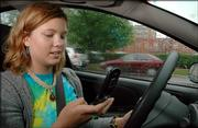 """Like many cell phone owners, Nena Grattan, KU freshman, St. Louis, sometimes uses her cell phone while driving. The city is considering a new fine for motorists who are guilty of inattentive driving while using a cell phone. """"That would be so hard to enforce,"""" said Grattan, Friday."""