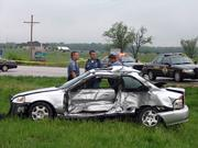 Douglas County Sheriff's officers work the scene of a fatal accident Saturday afternoon near the intersection of U.S Highways 59 and 56, about 10 miles south of Lawrence. The driver of the silver car was pronounced dead at the scene.