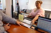 Payday Loans teller Stephanie McCullough, Shawnee, receives paperwork from a customer taking out a loan Friday afternoon at the 1401 W. Sixth St. location in Lawrence.
