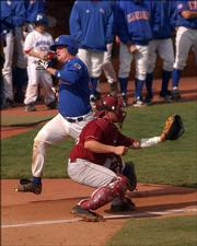 KU catcher Andrew Spitzfaden eludes OU's Jon Shackelford at home plate in the fifth inning of Game Two. The Jayhawks scored five runs that inning.