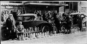Lawrence law enforcement pose with 200 quarts of illegal whiskey confiscated in a raid in this photo dated April 5, 1927. The photo was taken outside the police headquarters. The man seated on the running board is Will Johns, chief of police.