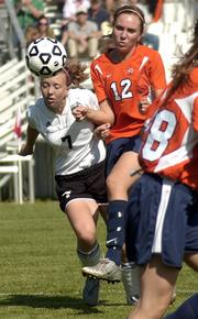 Free State High's Jenni Brooks (7) battles for the ball with Olathe East's Katie O'Keefe. The Hawks routed the Firebirds, 10-0, Tuesday at Free State.