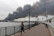 A jogger runs in Manhattan as a warehouse fire on the East River in Brooklyn, N.Y., sends plumes of thick black smoke over the city. Smoke from the 10-alarm fire could be seen for miles. The fire was the largest in New York City in at least a decade, excluding the World Trade Center attacks.