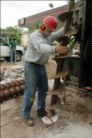 Jim Bieker, Lawrence, drills holes for inspection tubes for a service station across the street from 838 La., where a home was destroyed by a fire, caused by leaking gas.