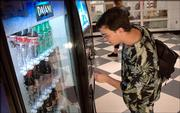 Lawrence High School sophomore Zach Guy selects a soft drink from a vending machine in the commons area at LHS. Soft drink companies on Wednesday announced that they will stop selling most sodas in the nation's public schools.