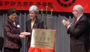Gov. Kathleen Sebelius shakes the hand of Wu Qidi, vice minister in China's Ministry of Education, while Kansas University Chancellor Robert Hemenway applauds during opening ceremonies for the Confucius Institute at KU's Edwards Campus in Overland Park. The Confucius Institute will offer community-based Chinese language instruction, and will support the professional development of Chinese language teachers and promote outreach programs on Chinese culture.