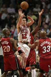 Chicago's Kirk Hinrich, center, releases a pass between Miami's Gary Payton, left, and Alonzo Mourning. The Heat won, 113-96, on Thursday night in Chicago to knock the Bulls out of the playoffs.