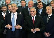 Israeli Prime Minister Ehud Olmert, front left, straightens his jacket as he stands with new ministers including Vice Premier Shimon Peres, middle front, and Israeli President Moshe Katsav, front right, during the official photo at the President's House in Jerusalem. Olmert was sworn in Thursday as Israel's prime minister, leading a coalition he hopes can carry out his main campaign pledge: to set permanent national borders by withdrawing Jewish settlers from parts of the West Bank.