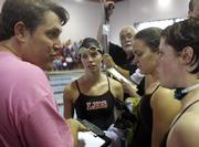 Lawrence High coach Ryan Adams, left, speaks with members of his swimming and diving squad during a break at the Sunflower Leage swim meet. Preliminary rounds were Friday at Knox Natatorium. The finals are slated for today.