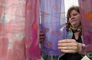 Lawrence artist Toni Brou arranges her hand-dyed scarves Sunday afternoon at Art in the Park.