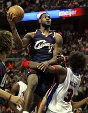 Cleveland forward LeBron James gets wrapped up - and fouled - by Detroit center Ben Wallace. The Pistons won Game 1 of their Eastern Conference quarterfinal, 113-86, on Sunday in Auburn Hills, Mich.