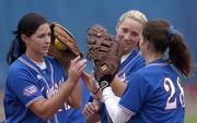Kansas University softball players, from left, Serena Settlemier, jessica moppin and nicole washburn, high-five each other before the beginning of the seventh inning against Iowa State. Sunday was senior day at Arrocha Ballpark, and Moppin and Settlemier played the last home game of their college careers, defeating Iowa State, 3-0.