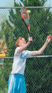 West's Chase Vervynck tosses up the serve at the Lawrence Invitational Tennis match. West took hole the  Junior High city tennis title.