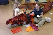 "Erika O&squot;Shea, left, and Jenn Crawford,wrap a 40-foot dragon in cloth and paper for this weekend&squot;s production of ""The Hobbit."""