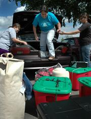 Tempest Mata, Haskell Indian Nations University freshman, Highland Village, Texas, from left, loads up her belongings with her mother, LaVelle Moalez, in the trunk of her car, and her sister Mi-Ya Mata, both of Highland Village. Haskell will have its commencement at 10 a.m. today.