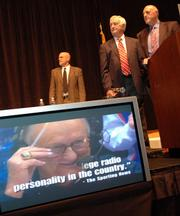 Max Falkenstien, top center, and Lew Perkins watch a video tribute.