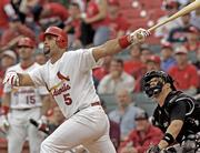 St. Louis first baseman Albert Pujols connects for a two-run home run against Colorado. Despite an aching back, Pujols, shown Wednesday in St. Louis, leads the major leagues in home runs and RBIs.