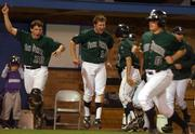 Free State High players Andy Petz (20) and Brett Lisher (14) celebrate the winning run against Lawrence High. The Firebirds scored the winning run in the bottom of the seventh inning, beating the Lions, 6-5, Thursday night at Hoglund Ballpark.