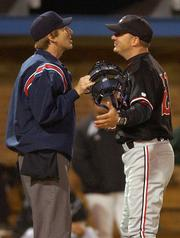 Lawrence High baseball coach Brad Stoll, right, argues a call with an umpire in the sixth inning. LHS fell to Free State, 6-5, Thursday at Hoglund Ballpark.