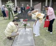 Family members gather Thursday in Miami at a cemetery marker that bears the names of  the 110 people who perished in May 1996 aboard ValuJet Flight 592 when the plane crashed in the Everglades.